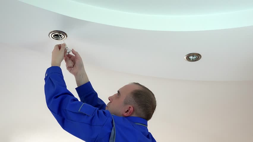 Worker man install or replace halogen light lamp into ceiling | Shutterstock HD Video #17575705