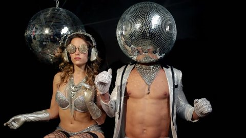 Two silver sexy disco characters. a male and female in sparkling silver costumes, the male has a discoball for a head
