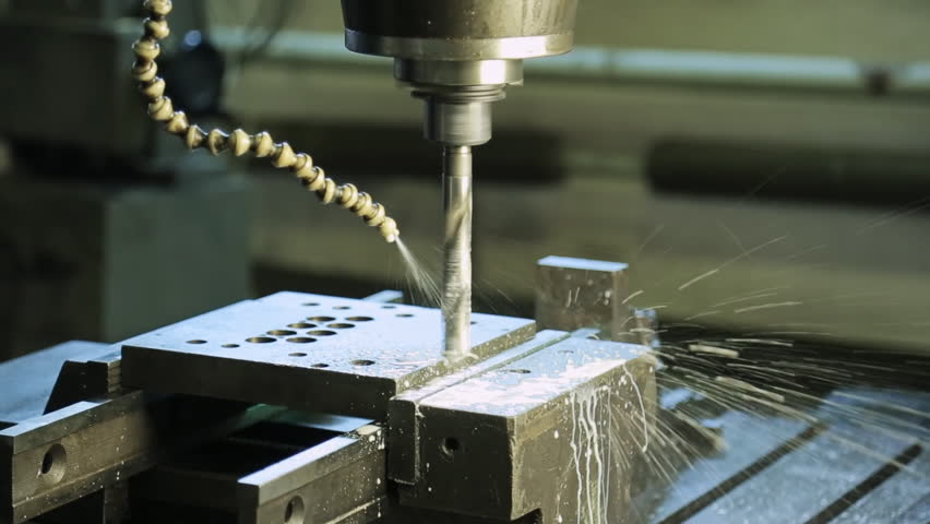 A running CNC machine with a rotating drill and a pipe for cutting fluid. #17587783