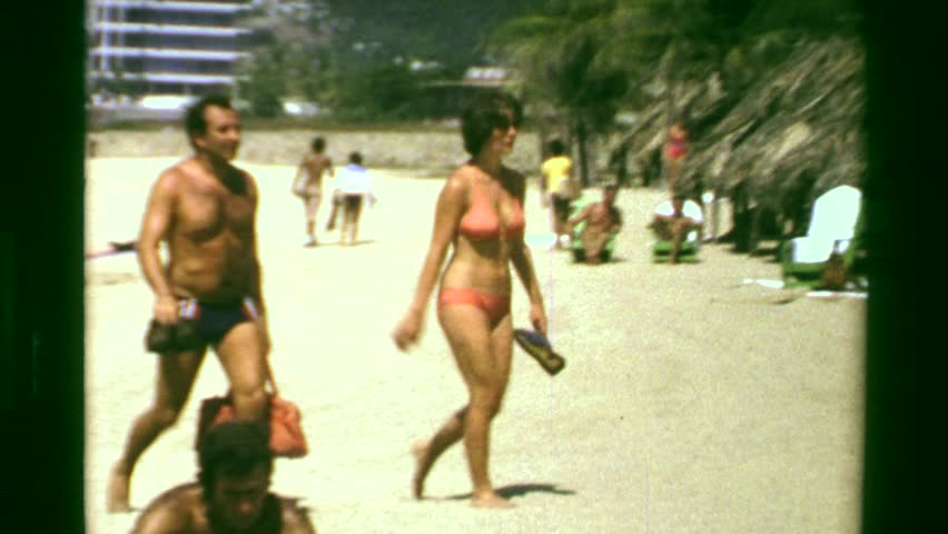 ACAPULCO, MEXICO 1978: Tan caucasian adult married couple walking white sand beach resort.