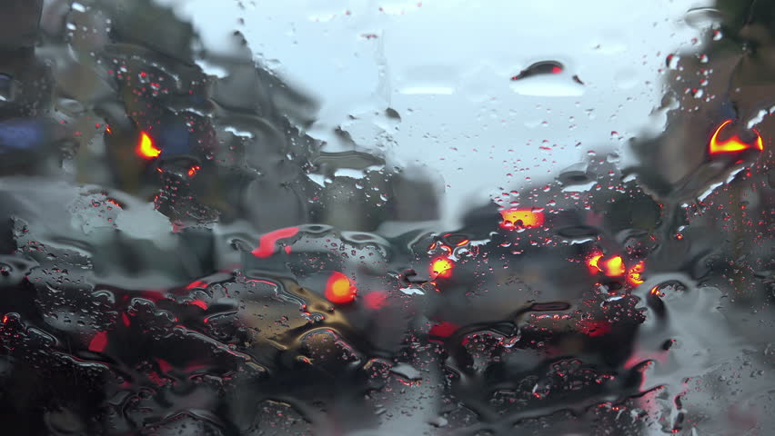 Cars queuing at the traffic lights under the rain: winter day in the city