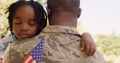American soldier is hugging his son in a park