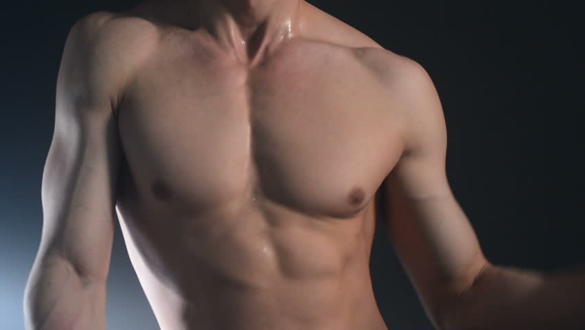 The body of young muscular sexy dancing male stripper on black background.  Cubes press on the abdomen