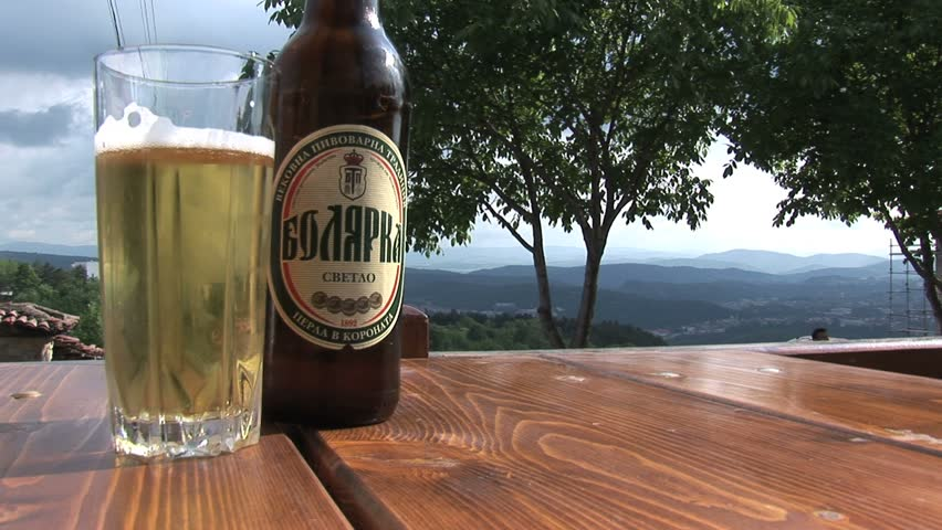 PLOVDIV, BULGARIA - CIRCA MAY 2007: A Bulgarian beer sits on a table overlooking a valley and mountains circa May 2007 in Plovdiv.