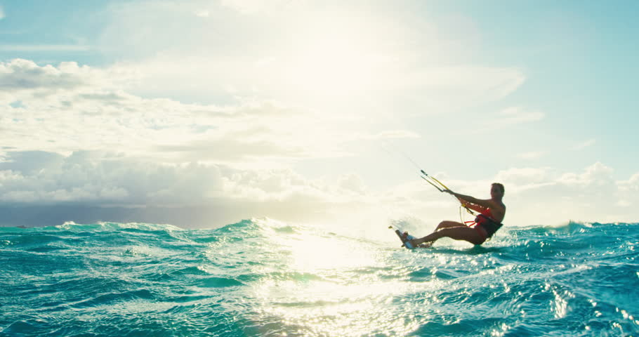 Beautiful young woman kiteboarding at sunset in slow motion, active lifestyle extreme sport