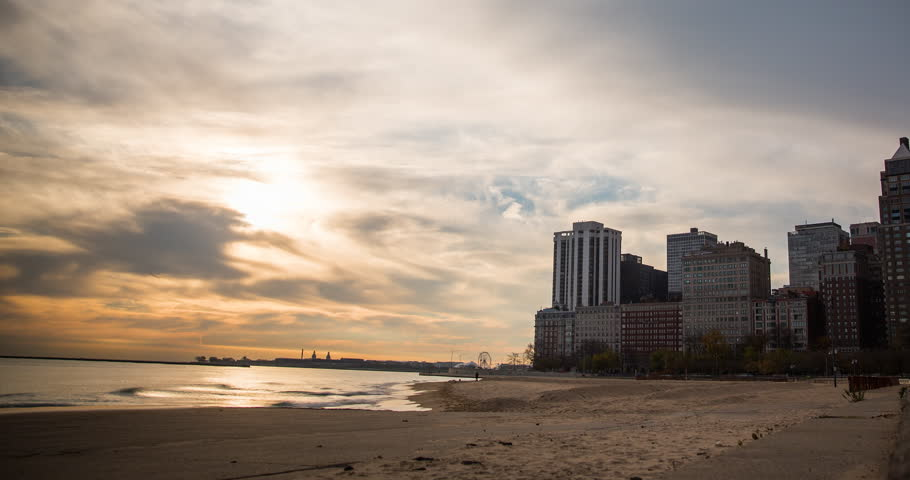 Chicago, Illinois, USA - view from the Oak Street Beach after sunrise with clouds and colorful sky at the shore of Lake Michigan - Timelapse with zoom out - October 2014