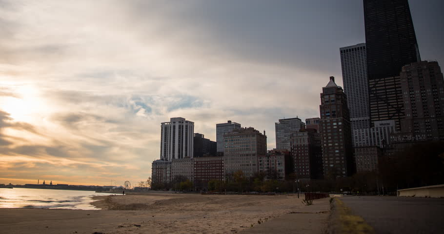 Chicago, Illinois, USA - view from Oak Street Beach after sunrise with clouds and colorful sky at the shore of Lake Michigan - Timelapse with pan right to left