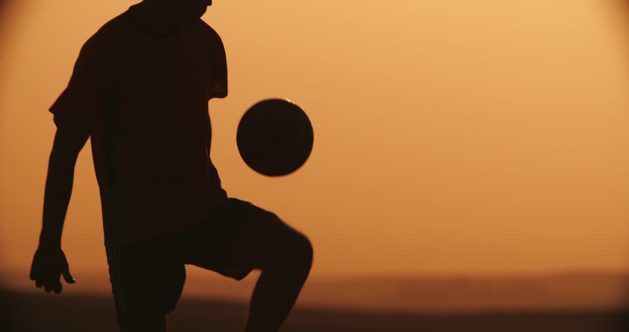 football player silhouette , practicing with the ball,the sunset Golden hour, slow motion