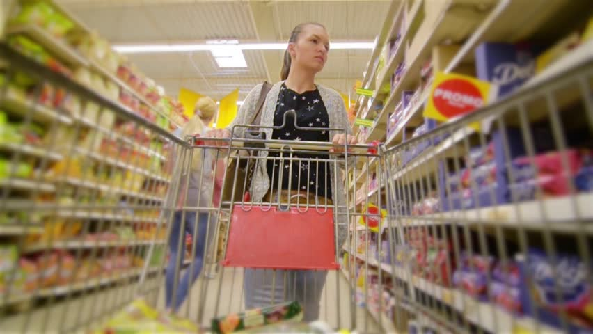 Caucasian woman walking along wholesale shelves and taking goods in shop trolley, beautiful young wife shopping in a supermarket | Shutterstock HD Video #17741134
