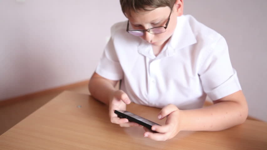 Teenager schoolboy playing phone sitting at the desk in the classroom. | Shutterstock HD Video #17759713
