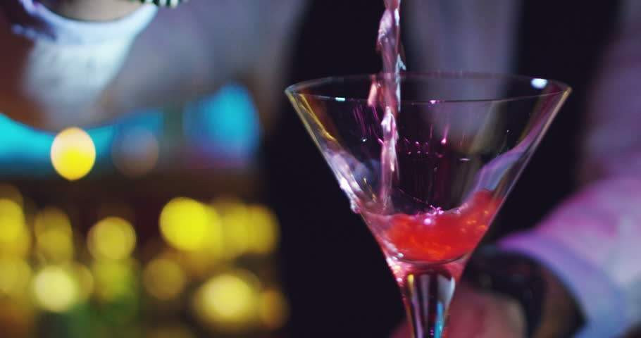 A young expert barman prepares a cocktail in a nightclub with a lot of experience and serves fresh and sweet taste.