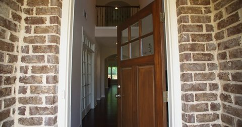 Front Home Entrance Low Angle Door Open Rise Up. rising low angle shot of the front entrance as the door opens to reveal the hallway of a modern residential home