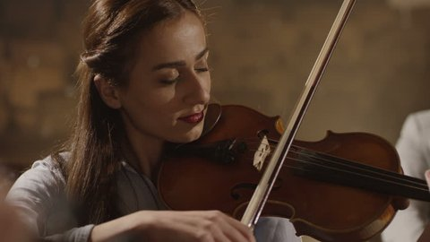 Close-up of musician playing violin on the symphony hall. Shot on RED EPIC Cinema Camera in slow motion.