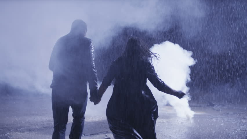Couple running  in heavy rain accross the smoke. Shot on RED EPIC Cinema Camera in slow motion.