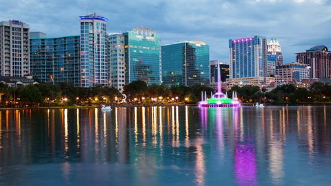 Orlando, Florida city skyline and water fountain at night in Lake Eola Park, timelapse