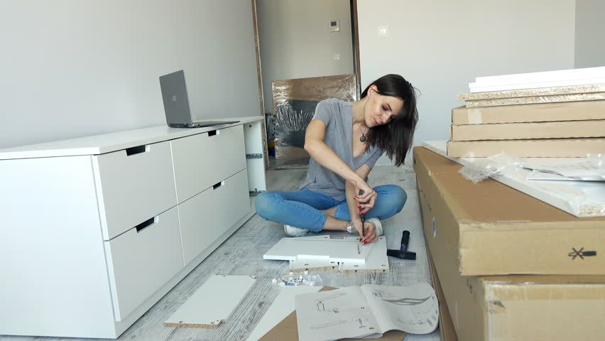 Young woman assembling furniture with screwdriver in her new home, 4K