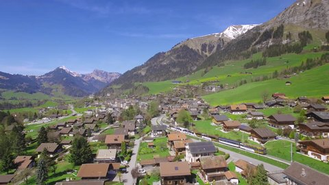 4K Golden Pass Train Switzerland aerial shot / Train arriving at Chateau-d'Oex in the Swiss Alps - Gruyere area