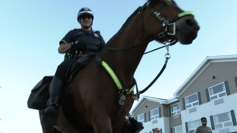 DULUTH, MINNESOTA - CIRCA 2016: Three police officers mounted on horses travel close by as they pass camera.