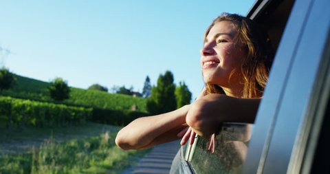 on a sunny day a beautiful woman puts the traveling head out the car window to admire the view and breathe pure air along with his friends that comes in her happy thoughts