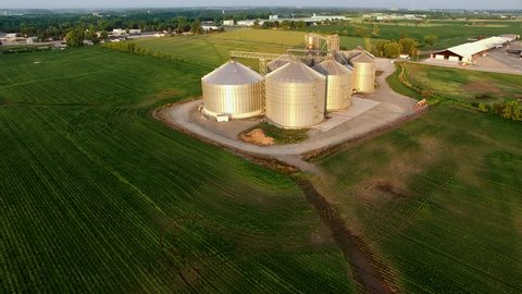 Aerial view of modern stainless steel agricultural grain silos at sunrise.