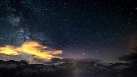 The apparent rotation of an outstandingly bright Milky Way and the starry sky beyond snowcapped mountain ridge, captured at high altitude in summertime on the Italian Alps. Time Lapse 4k video.