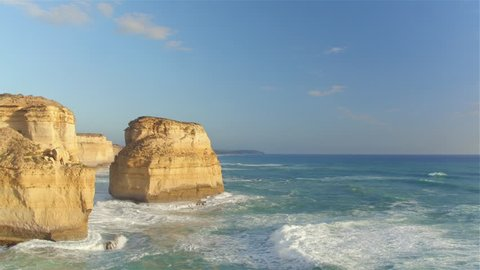 AERIAL, MOVING FORWARD: Flying along famous Twelve Apostles stack of limestone formations standing proudly in shallow turquoise sea towards rocky cliff coast at sunny Australian Great Ocean Road