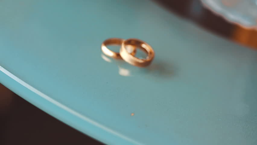 Wedding Rings On A Blue Marble Table   HD Stock Footage Clip