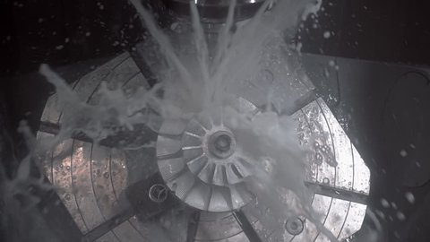The fluid cools the machined part on a milling machine. Slow motion, high speed camera, 250fps