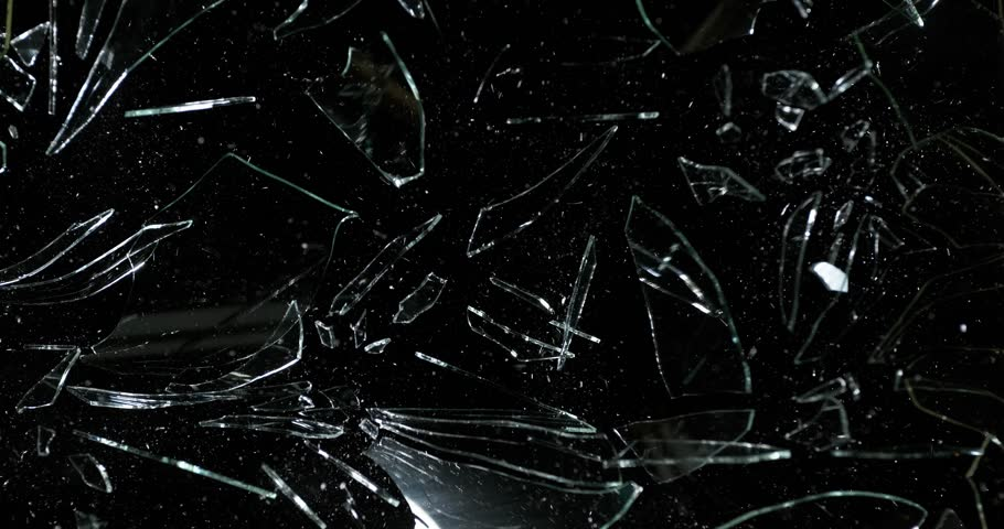 Stone breaking Pane of Glass against Black Background, Slow Motion