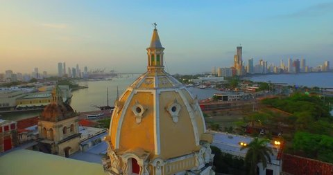 Aerial shot, flying over Cartagena near a domed church background sunset