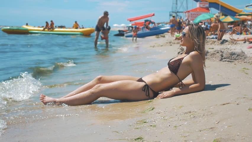 dfdcf775f08c7 Sexy slim girl in bikini having fun lying on shore of the beach in waves