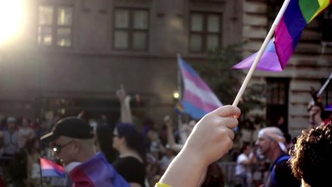 NEW YORK - JUNE 25, 2016: hands waving LGBT rainbow flags Gay Pride Parade in NYC. The march is held annually and attracts a large and diverse group of people.
