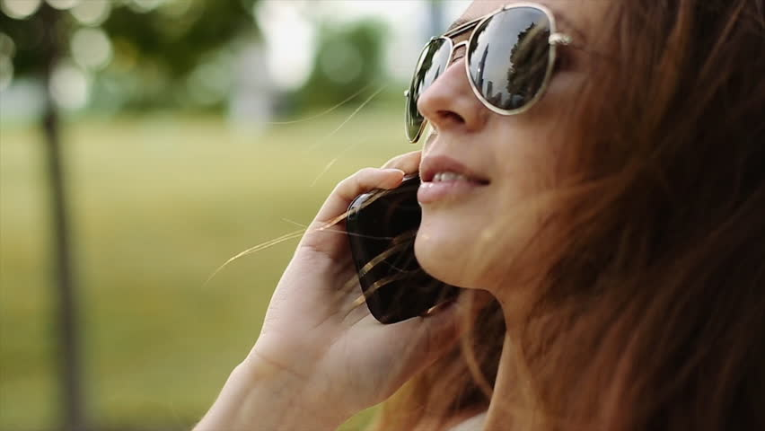 a Pretty Girl Talking on the Phone and Smiling in the Park. Petite Girl Have a Conversation by the Phone. Smiling Girl in White Shirt and Black Sunglasses Talking on the Phone and Laughing in the