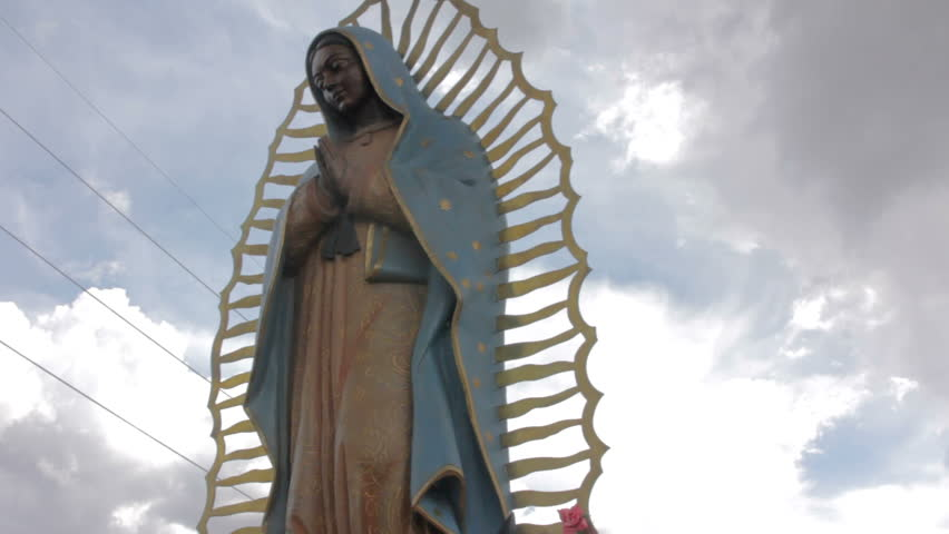 Low angle shot of of a statue of the Virgin of Guadalupe giving the symbol an imposing feeling. Dark clouds gather ominously behind the beautiful Mexican Catholic religious icon.