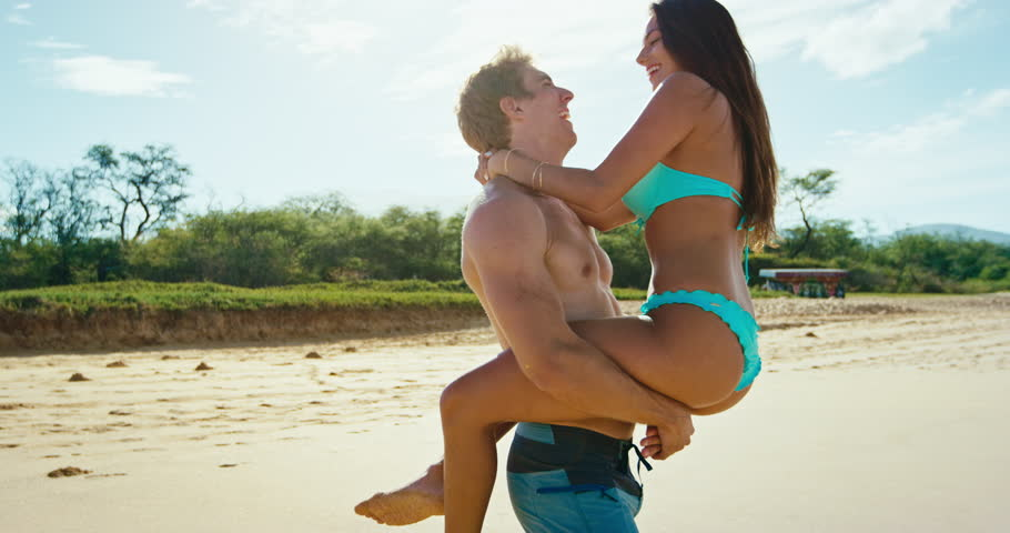 Romantic couple in love kissing and playing on the beach in slow motion