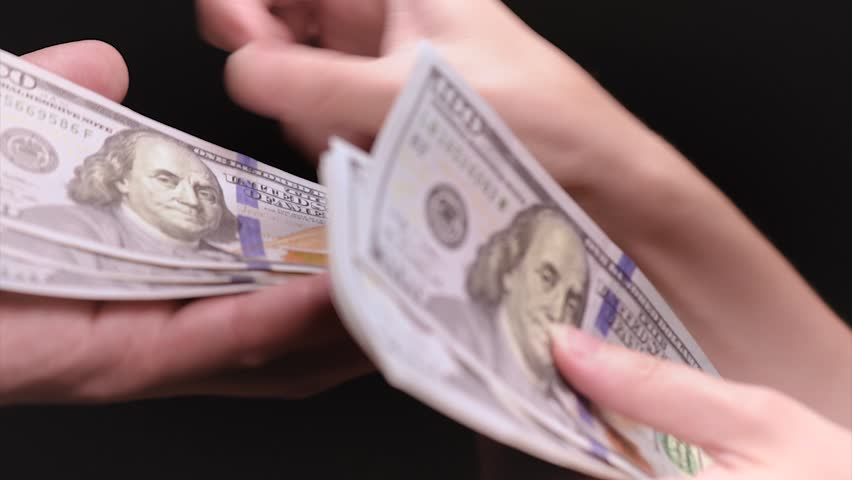 Female hands give US dollar banknotes for man or business partner. Woman accountant with money bills.