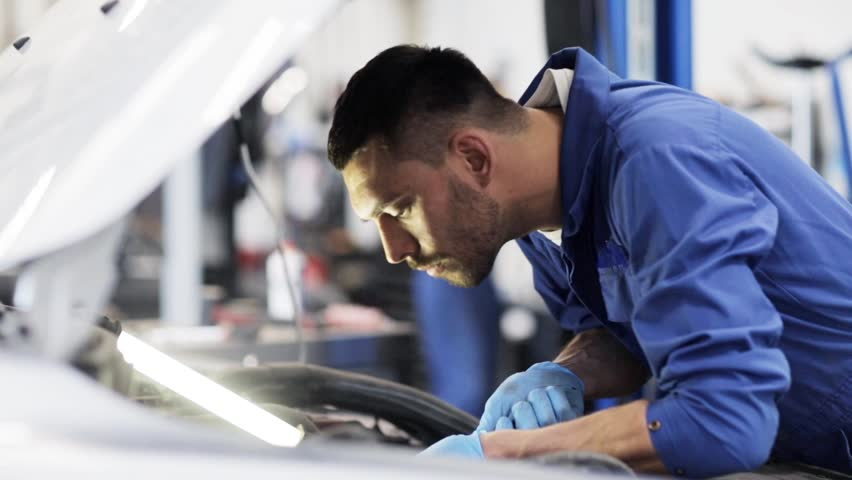Car service, repair, maintenance and people concept - mechanic man with wrench and lamp working at workshop | Shutterstock HD Video #18085303