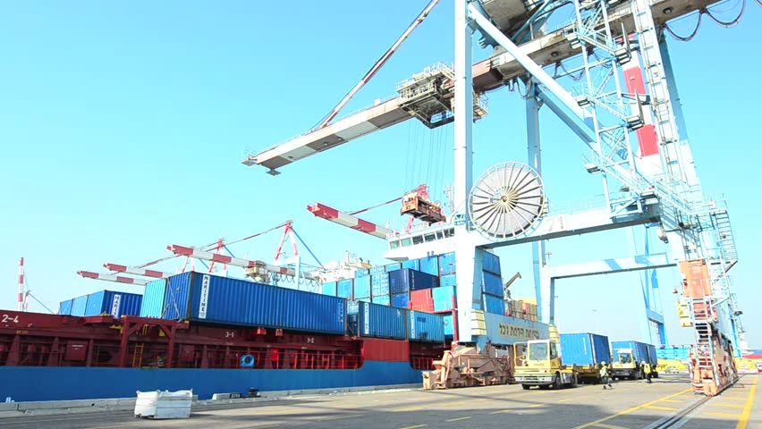 ASHDOD ISRAEL - DECEMBER 19: A cargo ship is loaded and unloaded by container crane in Ashdod seaport, Israel on December 19 2011.