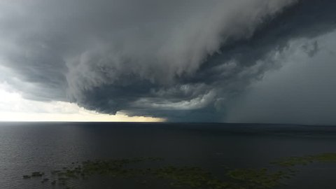 Aerial severe thunderstorm with large shelf cloud and rain core over Lake Okeechobee and Florida Everglades. Descending moving shot.