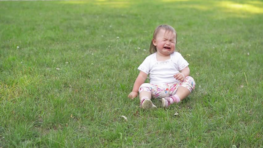 Children crying on green grass background, Small baby girl spending time outdoor on a warm summer day