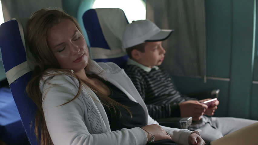Mother and son are flying in an airplane, Mother and son are flying in an airplane, son use a smartphone, mother sleep in armchair #18118153