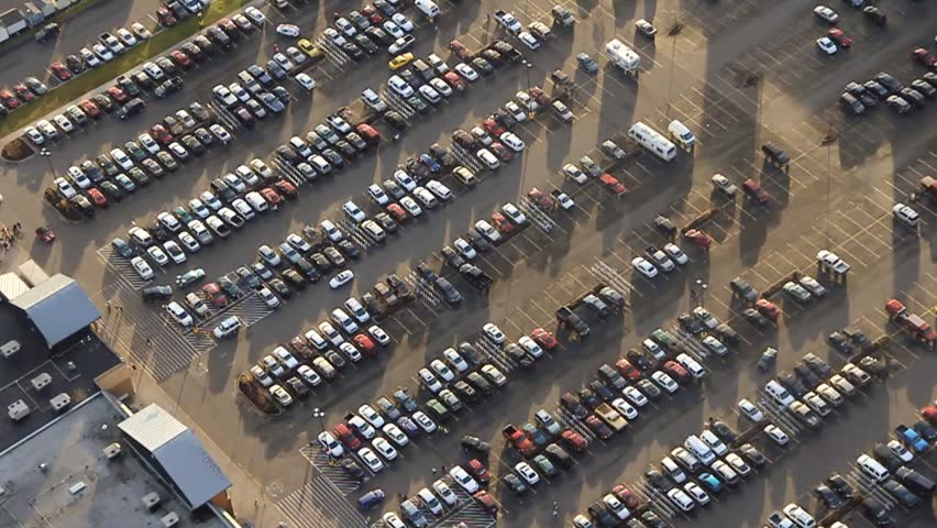 Circling aerial view of cars at shopping center parking lot before Christmas