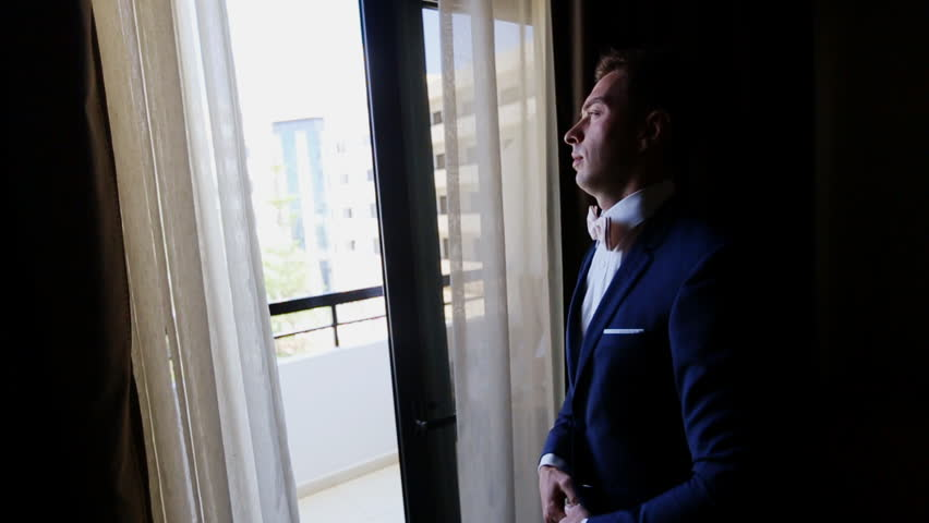 Attractive Man Straightens His Tie At The Window   HD Stock Video Clip
