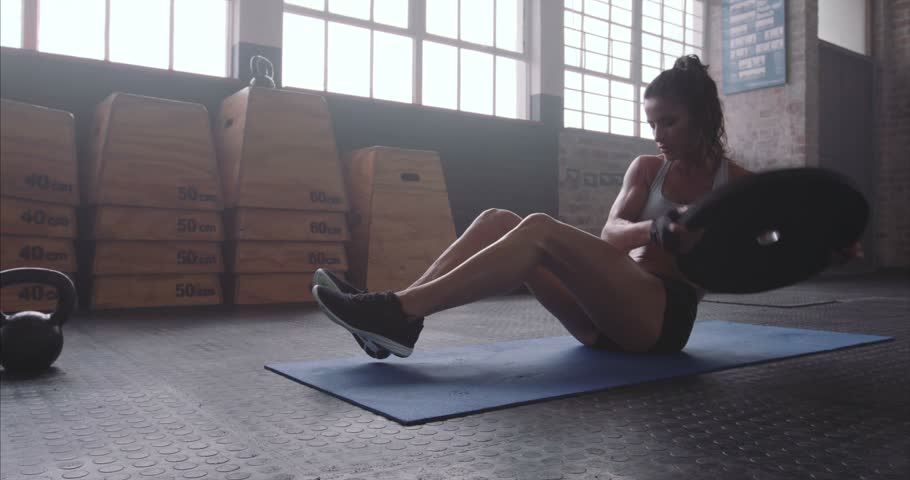 Muscular woman exercising with a weight plate. Fitness woman working out on core muscles at cross fit gym. Weight plate torso twist on exercise mat.    Shutterstock HD Video #18174223