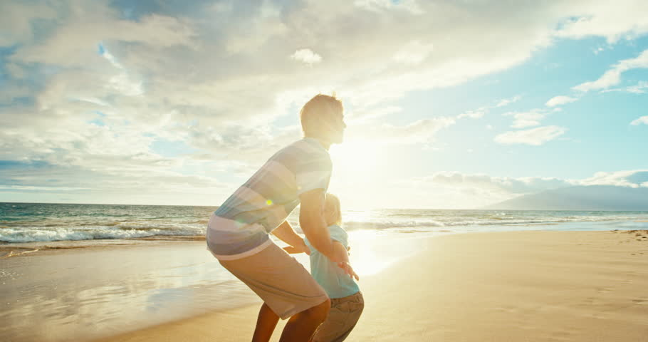 Father and son having fun on the beach at sunset, father throwing young boy up into the air | Shutterstock HD Video #18186568