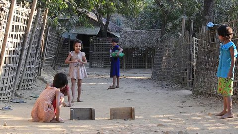 MRAUK-U, MYANMAR - JANUARY 27, 2016: Unidentified poor children playing outdoor game on the street. Poverty is a major issue in Burma
