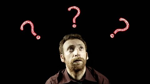 A lost doubtful man surrounded by animated question marks. Symbolic shot. Psychology, decisions, doubt.