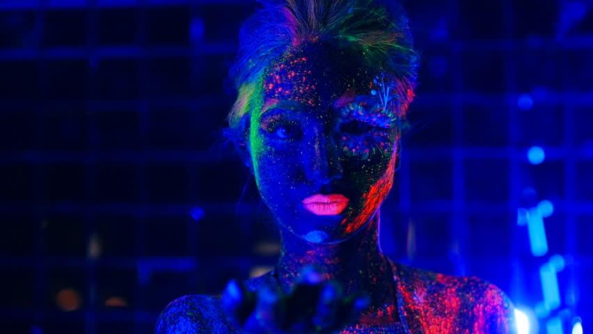 Girl in ultraviolet light blows green fluorescent powder with palm | Shutterstock HD Video #18251380