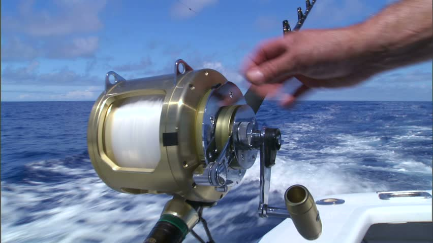 A sportfishing reel being wound by hand