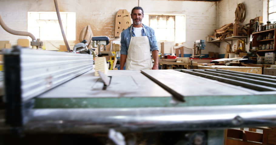 Carpenter smiling for camera in his work shop | Shutterstock HD Video #18271453
